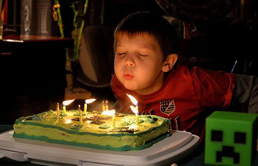 Kind bläst Kerzen auf Geburtstagskuchen aus
