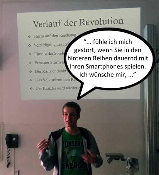Mann spricht vor einer Powerpoint-Folie, auf der etwas ganz anderes zu sehen ist.