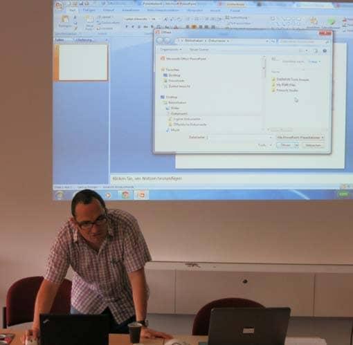 Person klickt vor einer PowerPoint-Oberfläche