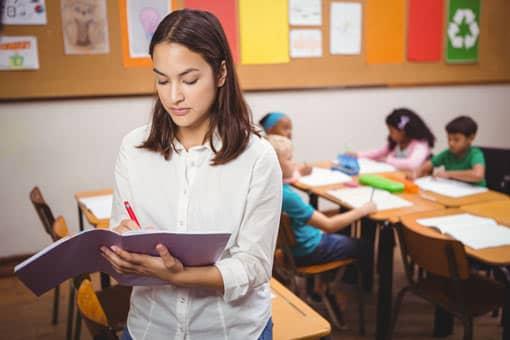 Lehrer korrigiert, während die Schüler arbeiten.