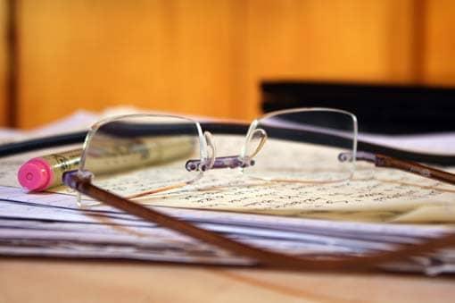 Stapel mit Korrekturen, Korrekturstift und Brille