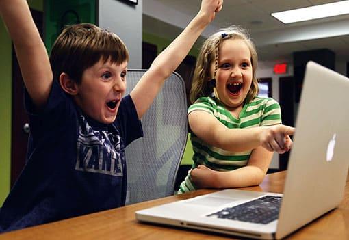 Mädchen und Junge vor dem Computer