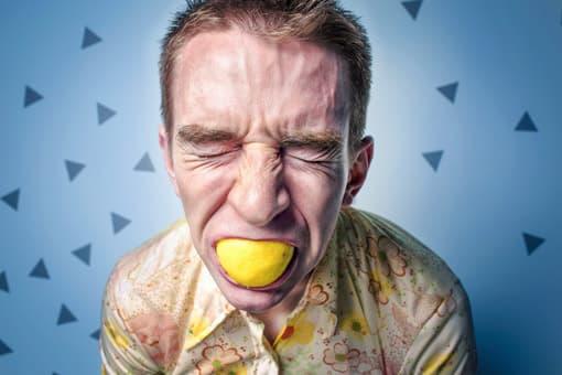 Mann beißt in eine Zitrone
