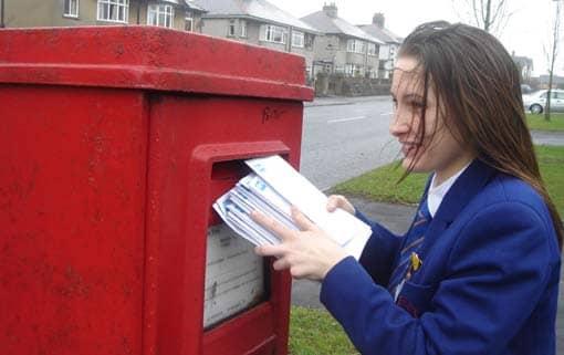 Frau wirft Briefe in einen Briefkasten