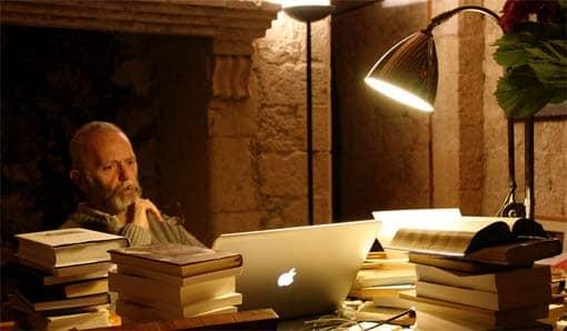 Mann führt Recherche mit Computer und Büchern durch