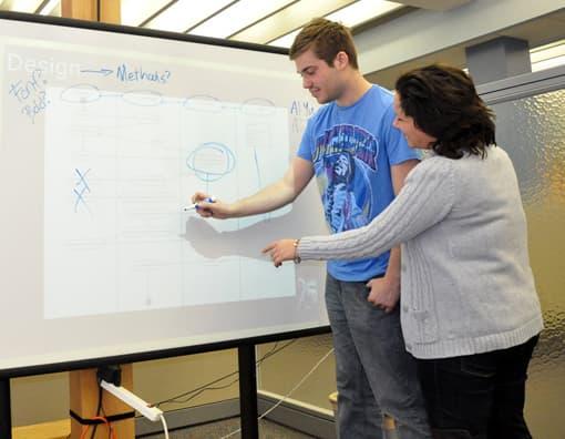 Lehrerin und Schüler an interaktivem Whiteboard