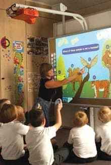 Bild: Kinder werden an einem interaktiven Whiteboard (ACTIVboard) unterrichtet