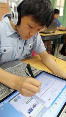 Südkoreanischer Junge beim Arbeiten am Laptop